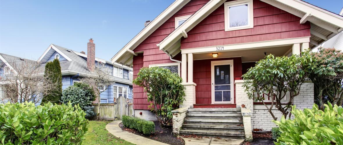 Craftsman-style single-family home with red and white exterior within a residential neighborhood.