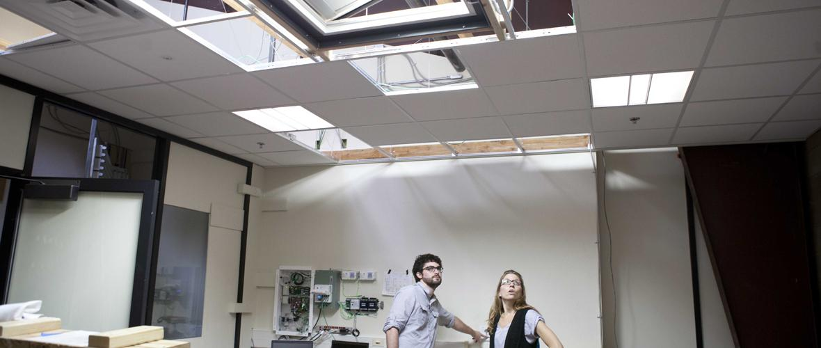 CLTC engineers examining lighting fixtures in the ceiling of the Advanced Daylighting Lab.