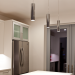 Interior of the Honda Smart Home US kitchen, with white walls and cabinetry, three pendant luminaires, and windowed doors.